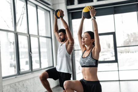 Photo for Athletic young man and woman in sportswear exercising with medicine balls in gym - Royalty Free Image