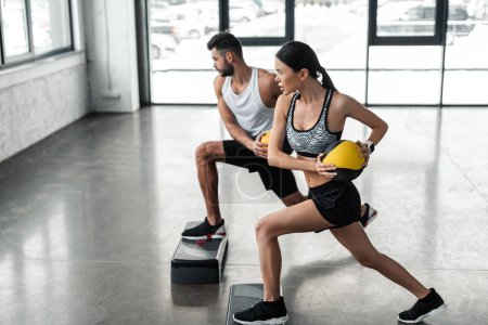 Photo for Side view of sportive young couple holding medicine balls and exercising on step platforms in gym - Royalty Free Image