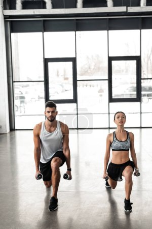 full length view of athletic young couple in sportswear exercising with dumbbells in gym