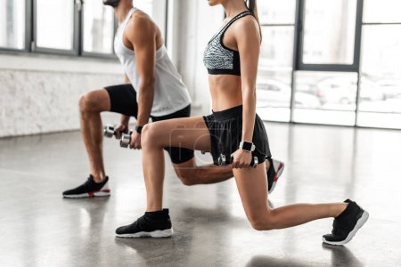 Photo for Cropped shot of sporty young couple exercising with dumbbells in gym - Royalty Free Image