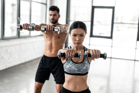 Photo for Young sporty man and woman holding dumbbells and training together in gym - Royalty Free Image