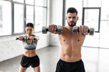 Foto de Joven pareja deportiva haciendo ejercicio con pesas en el gimnasio - Imagen libre de derechos