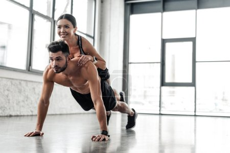 Photo for Muscular bare-chested sportsman doing push ups with smiling sporty girl on back in gym - Royalty Free Image