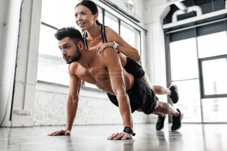 Photo for Muscular shirtless young man doing push ups with smiling sporty girl on back in gym - Royalty Free Image