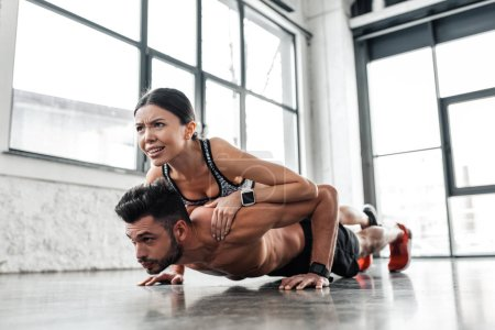 Photo for Muscular shirtless young man doing push ups with sporty girl on back in gym - Royalty Free Image