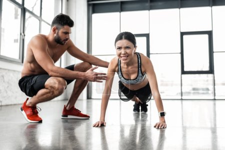 Photo for Muscular shirtless male trainer helping young sportswoman doing push ups in gym - Royalty Free Image
