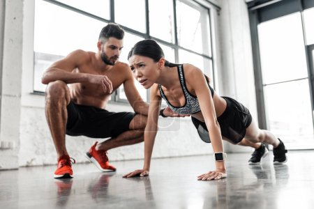 Photo for Muscular shirtless male trainer looking at young sportswoman doing push ups in gym - Royalty Free Image