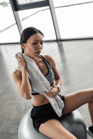 Photo pour Vue grand angle fatiguée fille sportive assis sur boule fit et essuyant la sueur avec serviette après entraînement en gymnase - image libre de droit