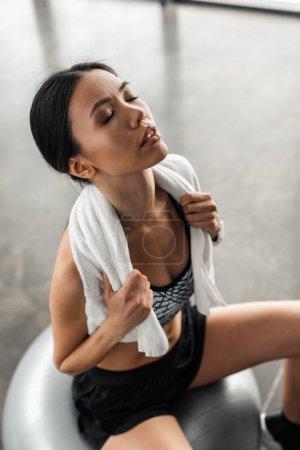 Photo pour Vue grand angle de la sportive épuisée avec serviette sur les épaules et les yeux fermés assis sur la balle en forme dans la salle de gym - image libre de droit