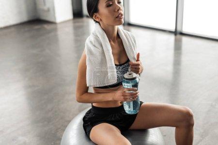 Photo pour Plan recadré de belle fille sportive avec serviette tenant bouteille d'eau et assis sur la balle en forme dans la salle de gym - image libre de droit