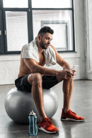 Photo for Young muscular bare-chested sportsman sitting on fit ball and using smartphone in gym - Royalty Free Image
