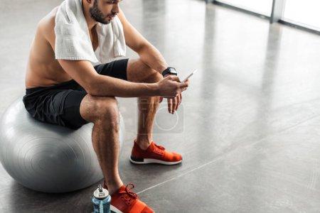 tiro recortado de hombre de pecho desnudo muscular sentado en la bola en forma y el uso de smartphone en el gimnasio