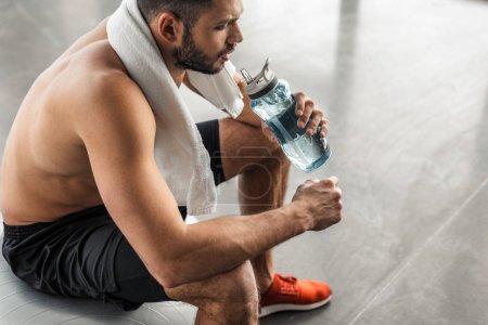 Photo pour Plan recadré d'un jeune sportif à poitrine nue avec une serviette assise sur une balle en forme et de l'eau potable dans un gymnase - image libre de droit