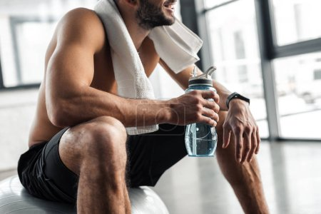 Photo for Cropped shot of shirtless sportsman with towel and bottle of water sitting on fit ball in gym - Royalty Free Image