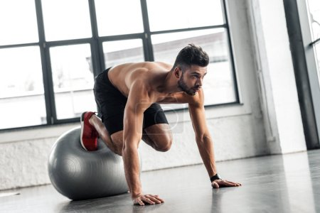 Photo for Young bare-chested sportsman exercising on fitness ball in gym - Royalty Free Image