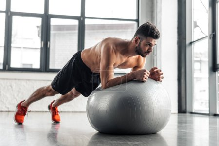 Photo for Muscular shirtless young man doing plank exercise on fitness ball at gym - Royalty Free Image