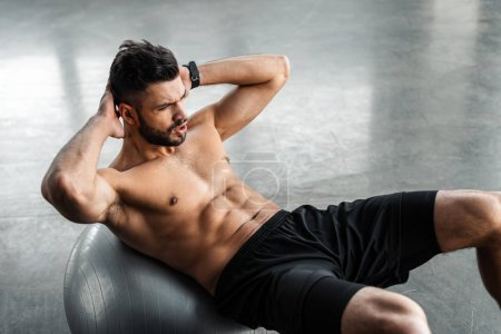 Photo for High angle view of young sportsman with bare chest doing abs exercise on fitness ball at gym - Royalty Free Image