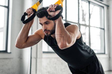 Foto de Concentrado deportivo guapo colgando en vendas de la resistencia y mirando lejos en gimnasio - Imagen libre de derechos