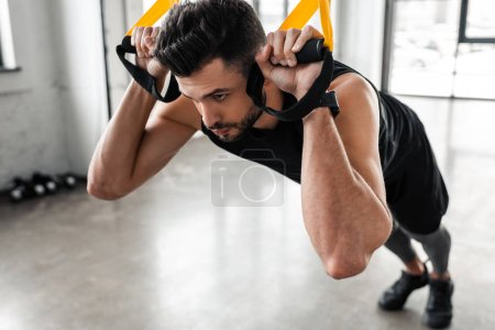 Photo for Close-up view of concentrated sporty man hanging on fitness straps and looking away in gym - Royalty Free Image