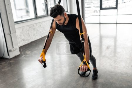Photo for High angle view of muscular young man exercising with resistance bands in gym - Royalty Free Image