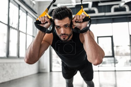 Photo for Handsome concentrated sporty man hanging and training with fitness straps in gym - Royalty Free Image