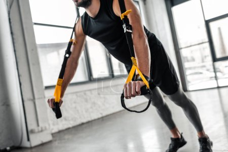 Foto de Recortar foto de hombre joven en ropa deportiva ejercicio con bandas de resistencia en gimnasio - Imagen libre de derechos