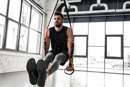 Photo for Handsome muscular young sportsman exercising with suspension straps in gym - Royalty Free Image