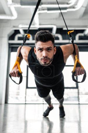 Foto de Guapo joven deportista serio colgando y entrenamiento con bandas de resistencia en gimnasio - Imagen libre de derechos