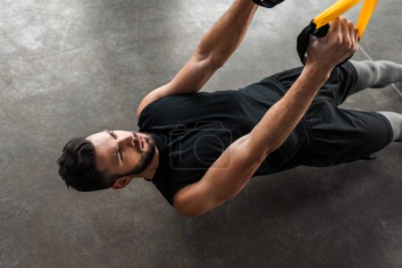Photo for High angle view of concentrated muscular young man training with suspension straps in gym - Royalty Free Image