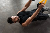 high angle view of concentrated muscular young man training with suspension straps in gym