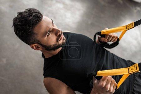 Photo pour Vue d'angle élevé de concentré jeune homme formation avec sangles de remise en forme dans la salle de gym - image libre de droit