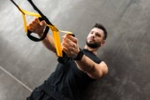 high angle view of muscular young man in sportswear hanging and training with resistance bands in gym