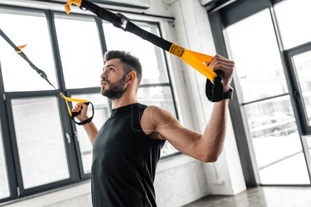 Photo for Athletic young man in sportswear training with suspension straps and looking up in gym - Royalty Free Image