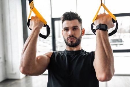 Photo pour Beau musclé sportif jeune formation avec sangles de suspension dans la salle de gym - image libre de droit