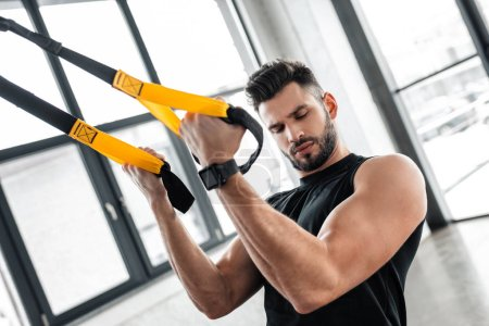 Photo for Handsome muscular young man looking at biceps while training with suspension straps in gym - Royalty Free Image