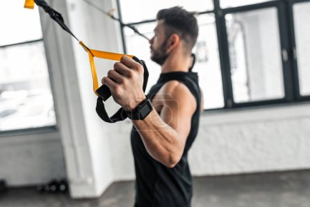 Photo for Side view of muscular young man in sportswear training with resistance bands in gym - Royalty Free Image