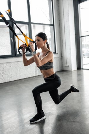 Photo for Full length view of sporty focused girl training with fitness straps in gym - Royalty Free Image