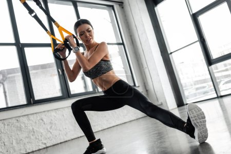 athletic young woman training with resistance bands and stretching legs in gym