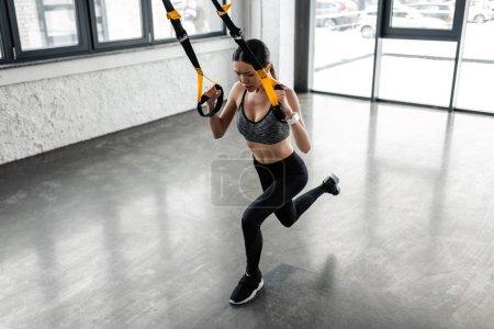 Foto de Vista de ángulo alto de joven deportista ejercicio con las correas de suspensión en gimnasio - Imagen libre de derechos