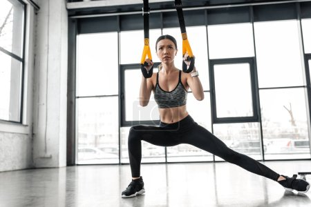 Photo for Beautiful athletic girl in sportswear training with resistance bands in gym - Royalty Free Image