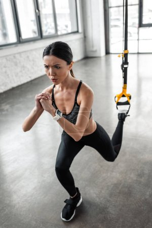 Photo for High angle view of concentrated young sportswoman training with suspension straps in gym - Royalty Free Image