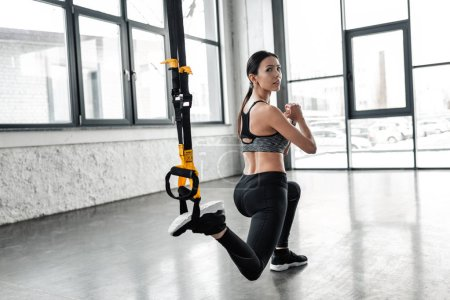 Photo for Athletic young woman in sportswear training with resistance bands and looking at camera in gym - Royalty Free Image