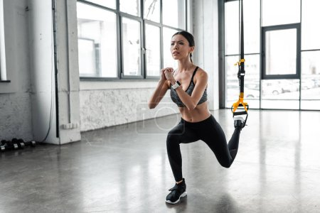 Photo for Attractive young sportswoman exercising with fitness straps in gym - Royalty Free Image