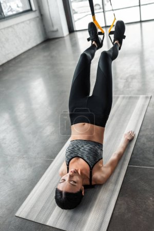 Photo for Beautiful young woman exercising with resistance bands on yoga mat in gym - Royalty Free Image