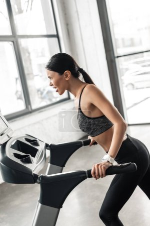 Photo for Side view of athletic young woman training on treadmill in gym - Royalty Free Image