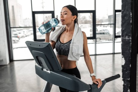Photo for Beautiful young sportswoman with towel on shoulders standing on treadmill and drinking water in gym - Royalty Free Image