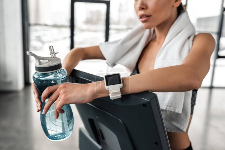 Photo for Cropped shot of young sportswoman holding bottle of water and leaning at treadmill in gym - Royalty Free Image
