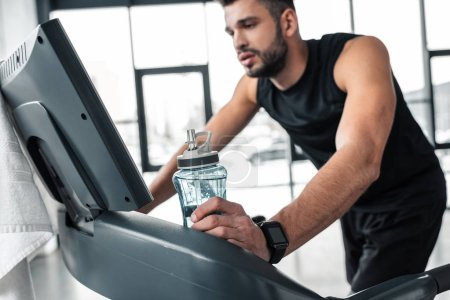 Photo for Exhausted young sportsman with smartwatch holding bottle of water and training on treadmill in gym - Royalty Free Image