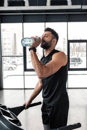 Photo for Athletic young man drinking water while standing on treadmill in gym - Royalty Free Image