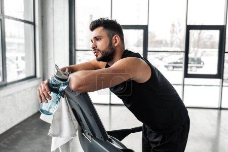 Photo pour Épuisé de jeune sportif se penchant au tapis roulant et tenant la gourde de sport avec de l'eau dans la salle de gym - image libre de droit